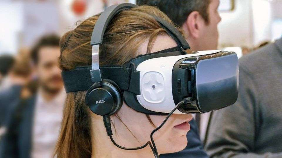 Ein braunhaariges Mädchen hat eine VR-Brille und Kopfhörer auf