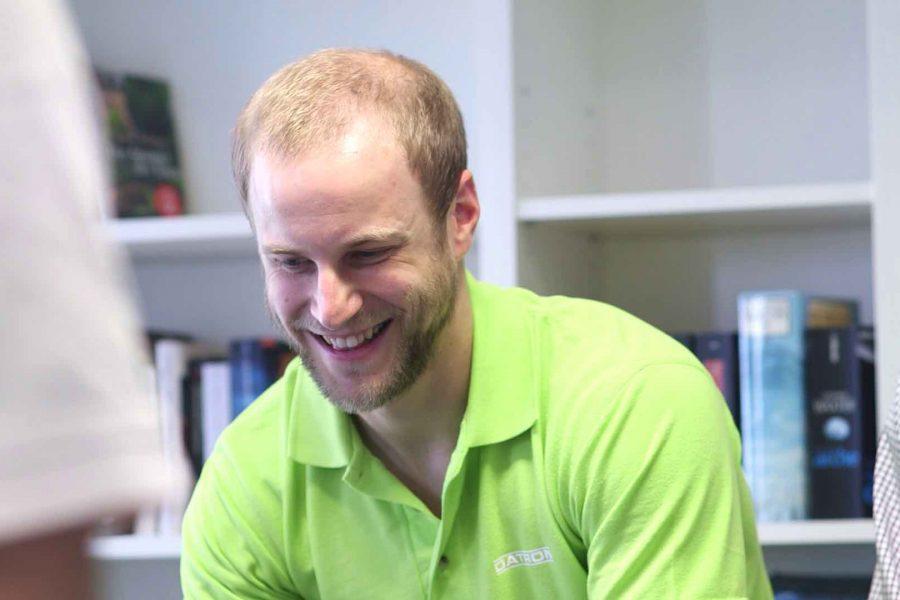 Ein DATRON-Mitarbeiter schaut sich mit anderen Personen etwas an und lacht