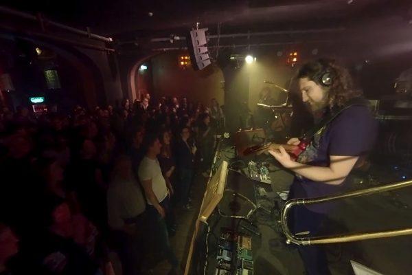 Menschen stehen vor der Bühne auf der eine Band spielt
