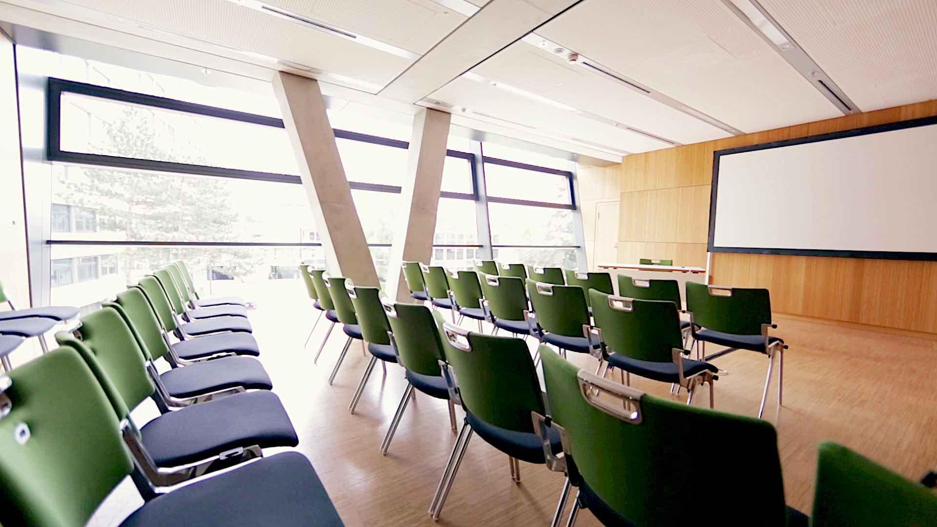 Ein leerer Vortragsraum mit grünen Stühlen
