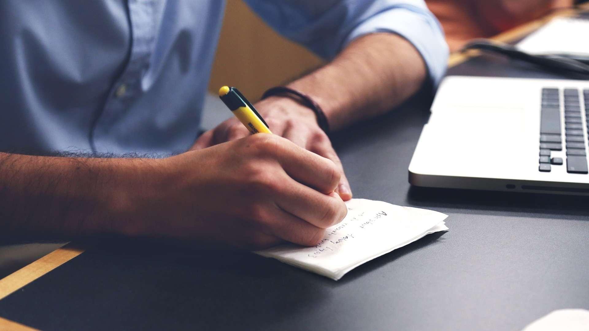 Ein Mann sitzt vor einem Laptop und schreibt auf Zettel, die neben ihm liegen