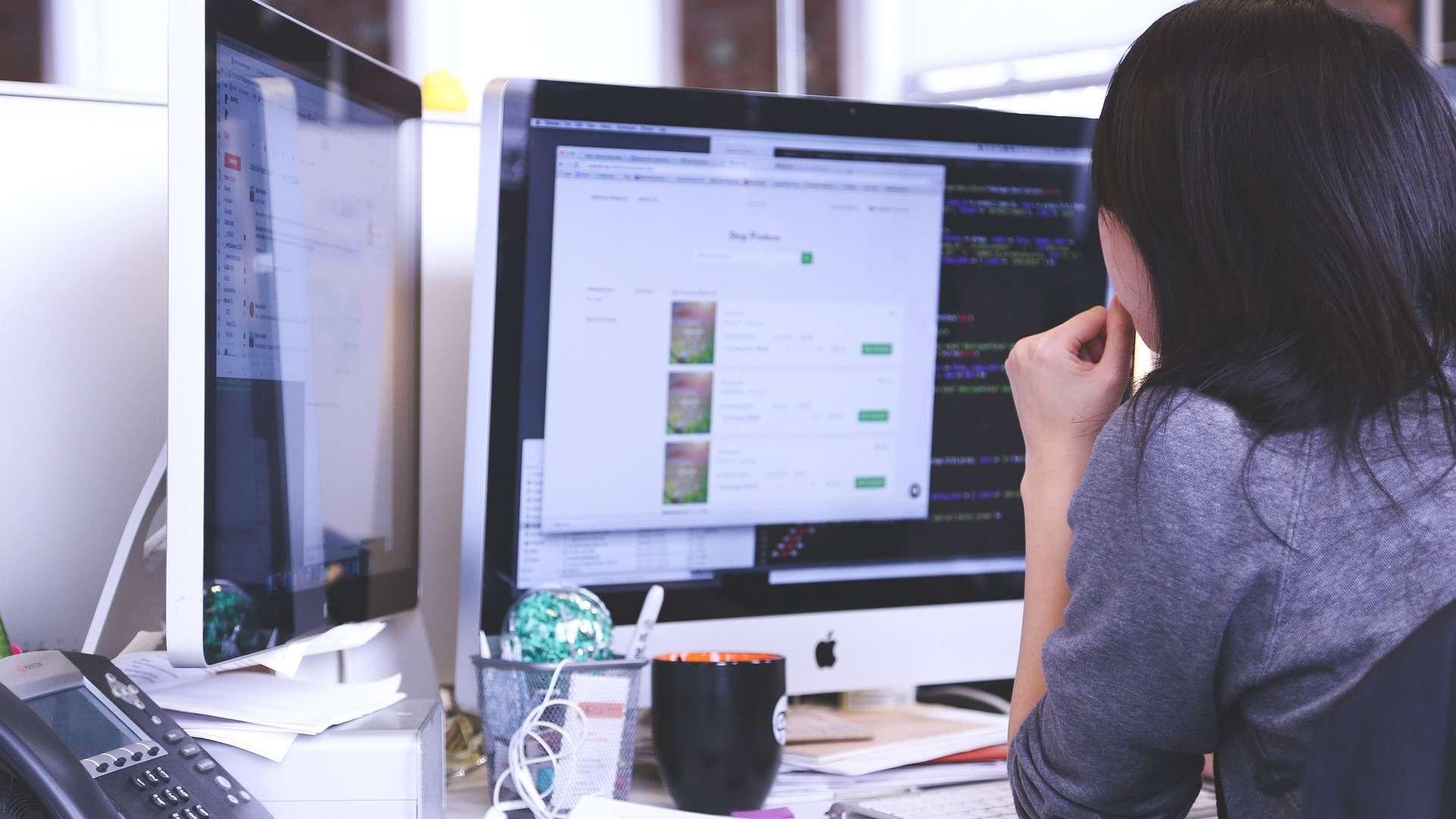 Ein Frau sitzt an einem Schreibtisch vor zwei iMacs und arbeitet