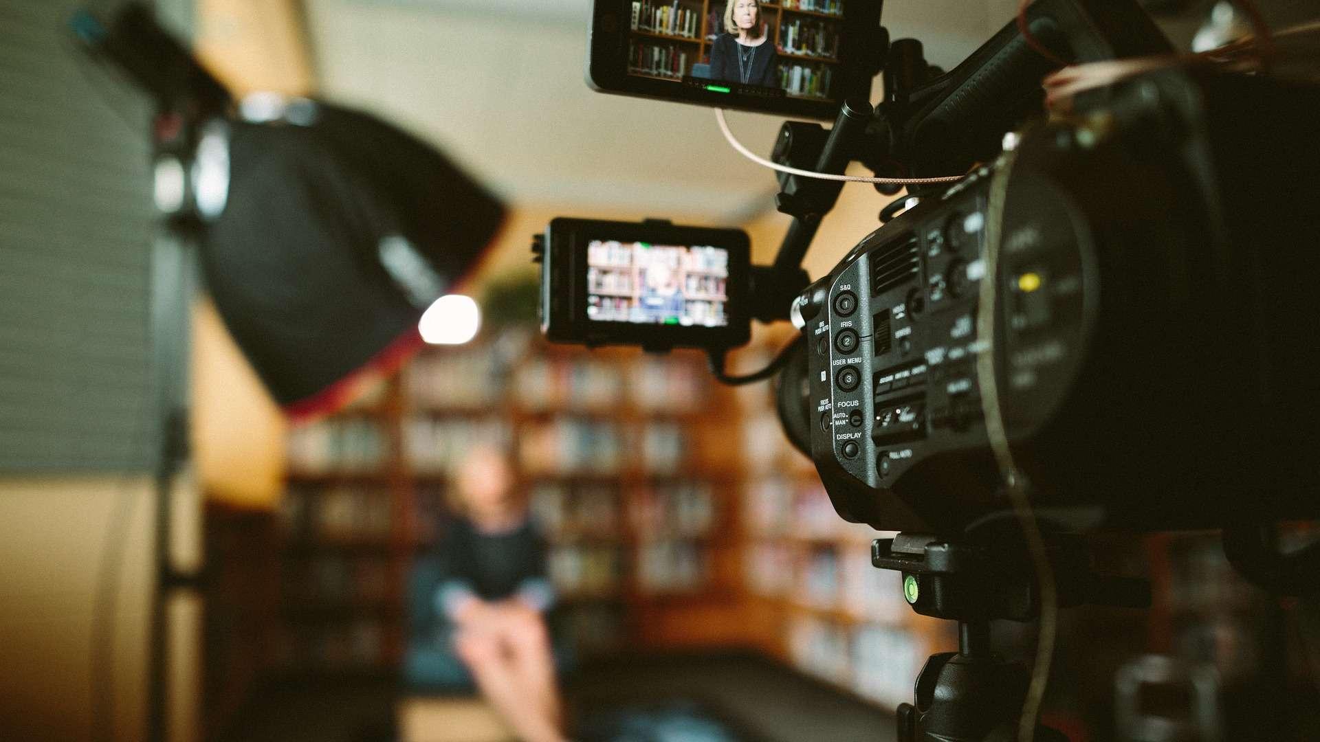 Seitliche Perspektive auf eine Kamera, die ein Interview mit einer Frau in einer Bibliothek filmt