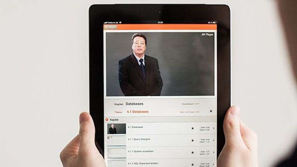 Zwei Hände halten ein Tablet, auf dem ein Video-Handbuch abgespielt wird