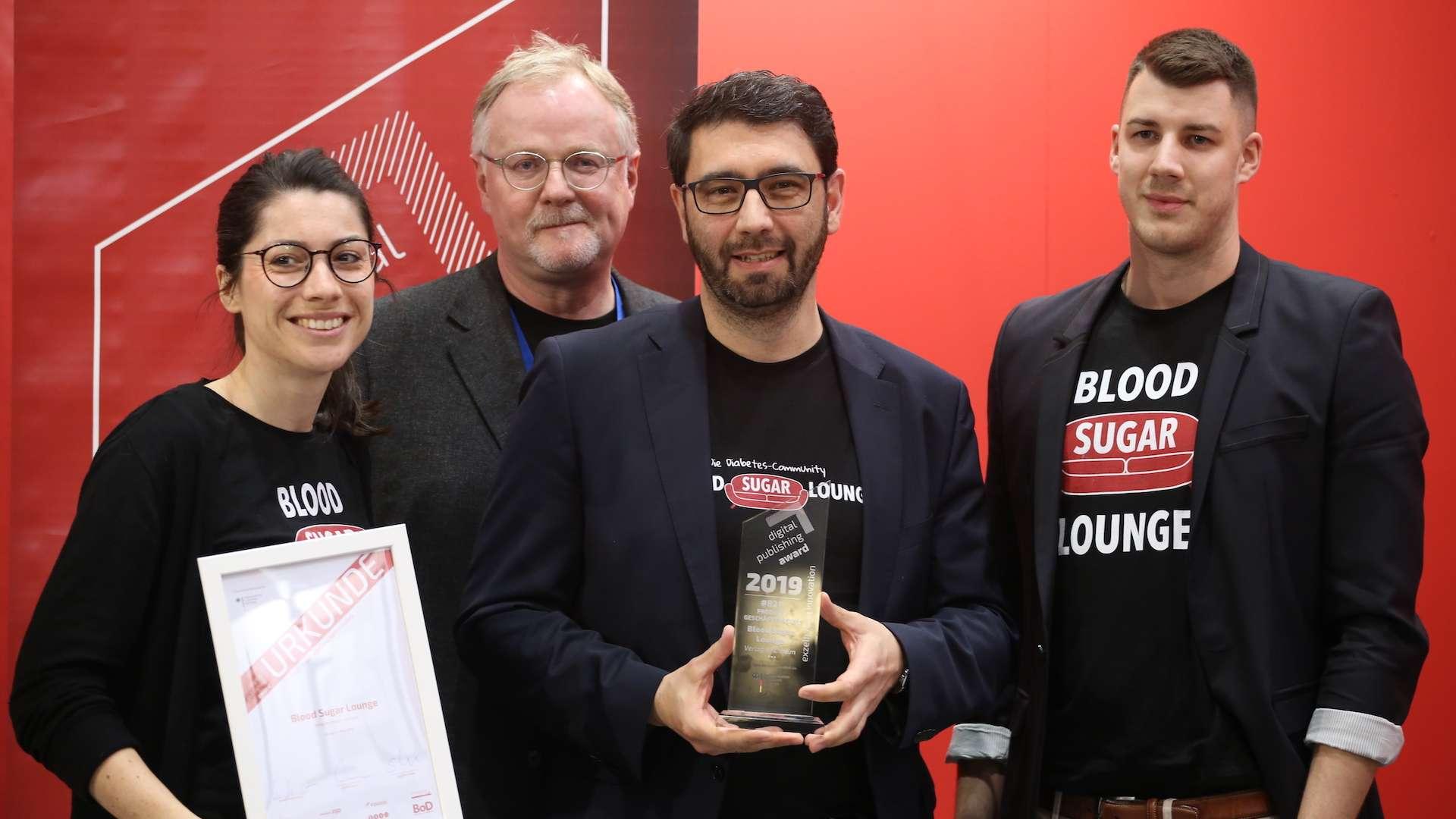 Vier Mitarbeiter der Blood Sugar Lounge stehen vor einem roten Hintergrund und präsentieren den gewonnen digital publishing award