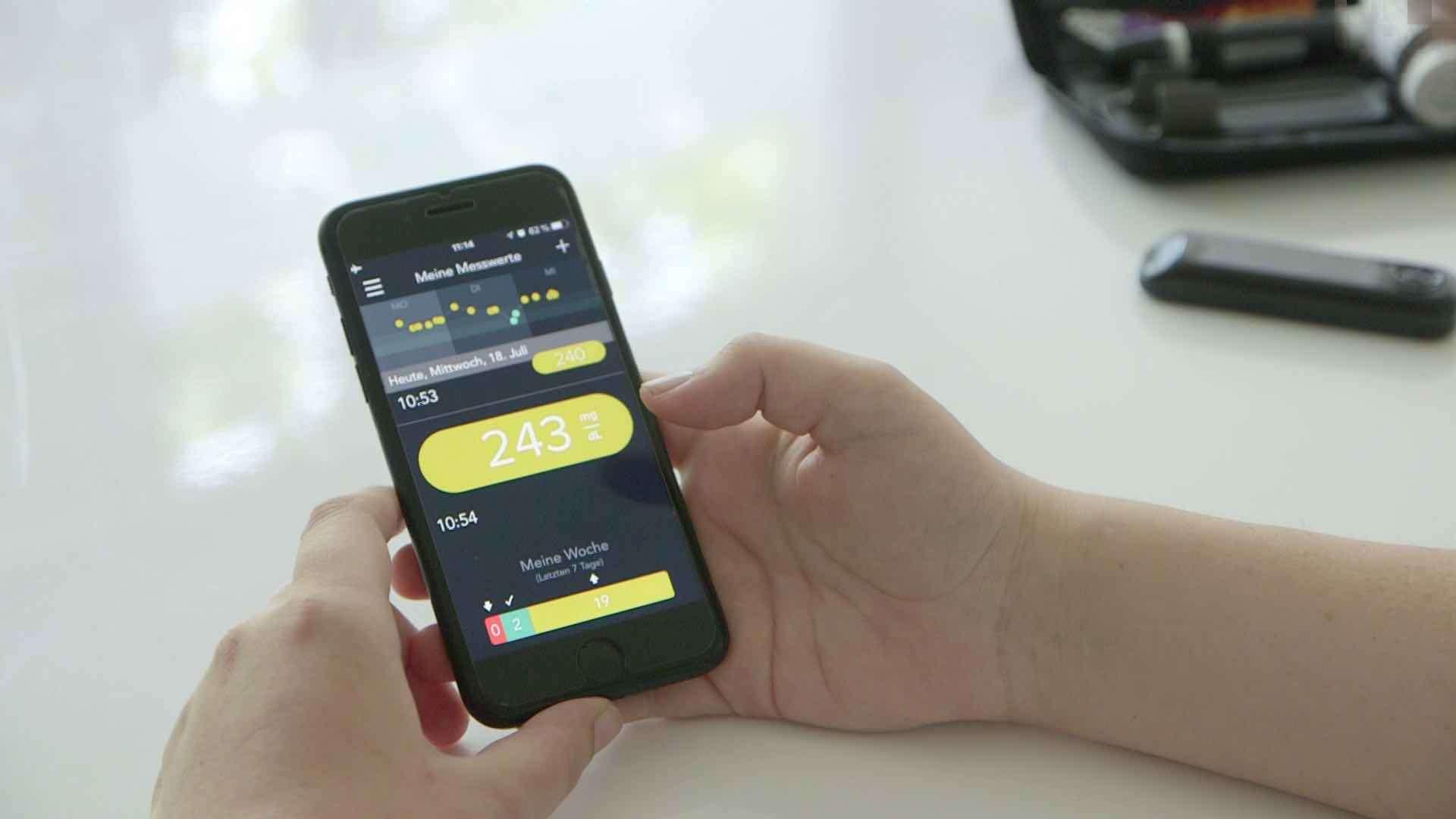 Eine Person hält ein iPhone und schaut sich Messwerte an