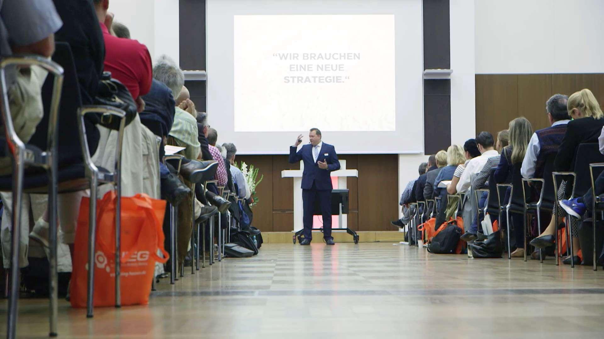 Ein Mann hält einen Vortrag in einem großen Raum voller sitzender Menschen