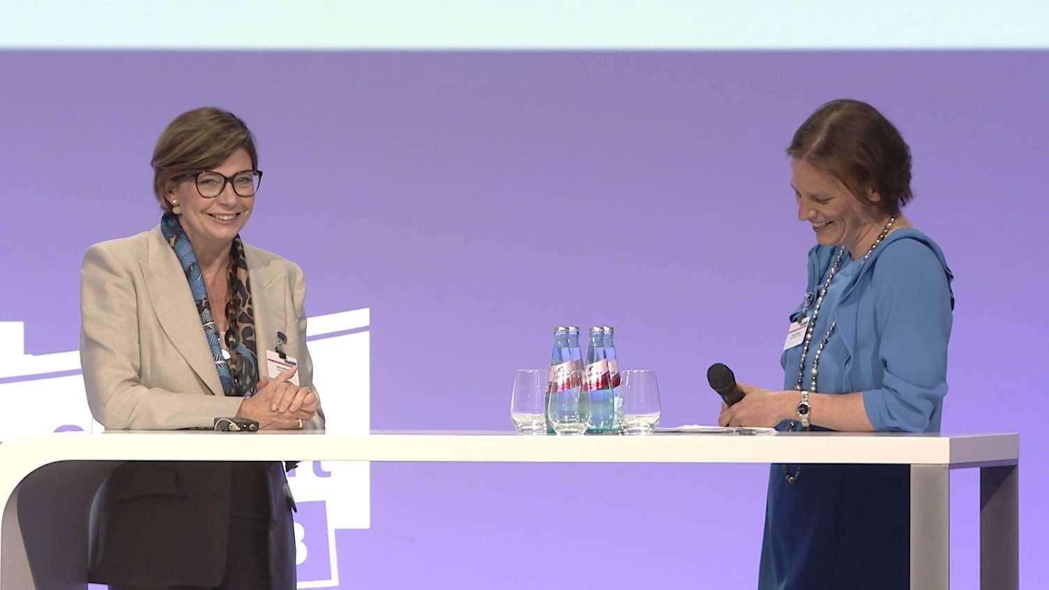 Zwei Frauen stehen an einem Tisch und führen ein Interview