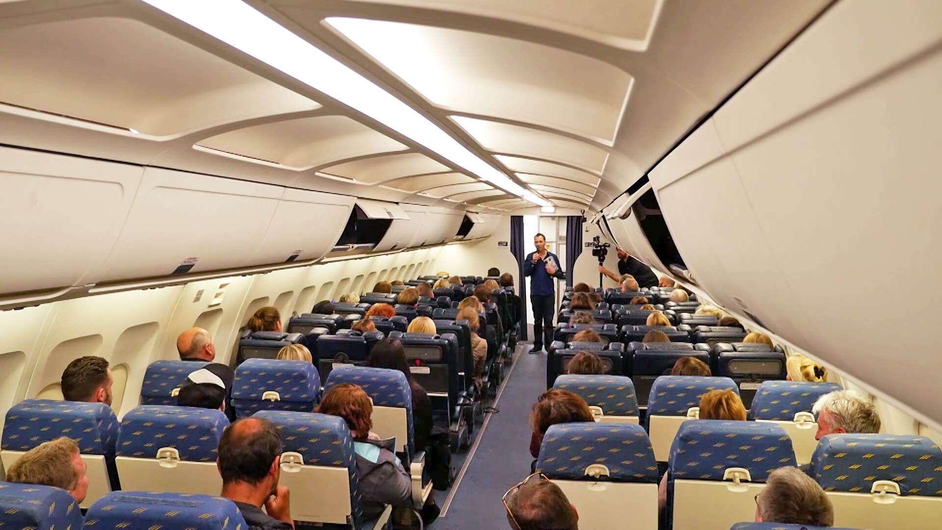 Der Autor Sebastian Fitzek stellt in einem Flugzeug sein Buch Flugangst vor