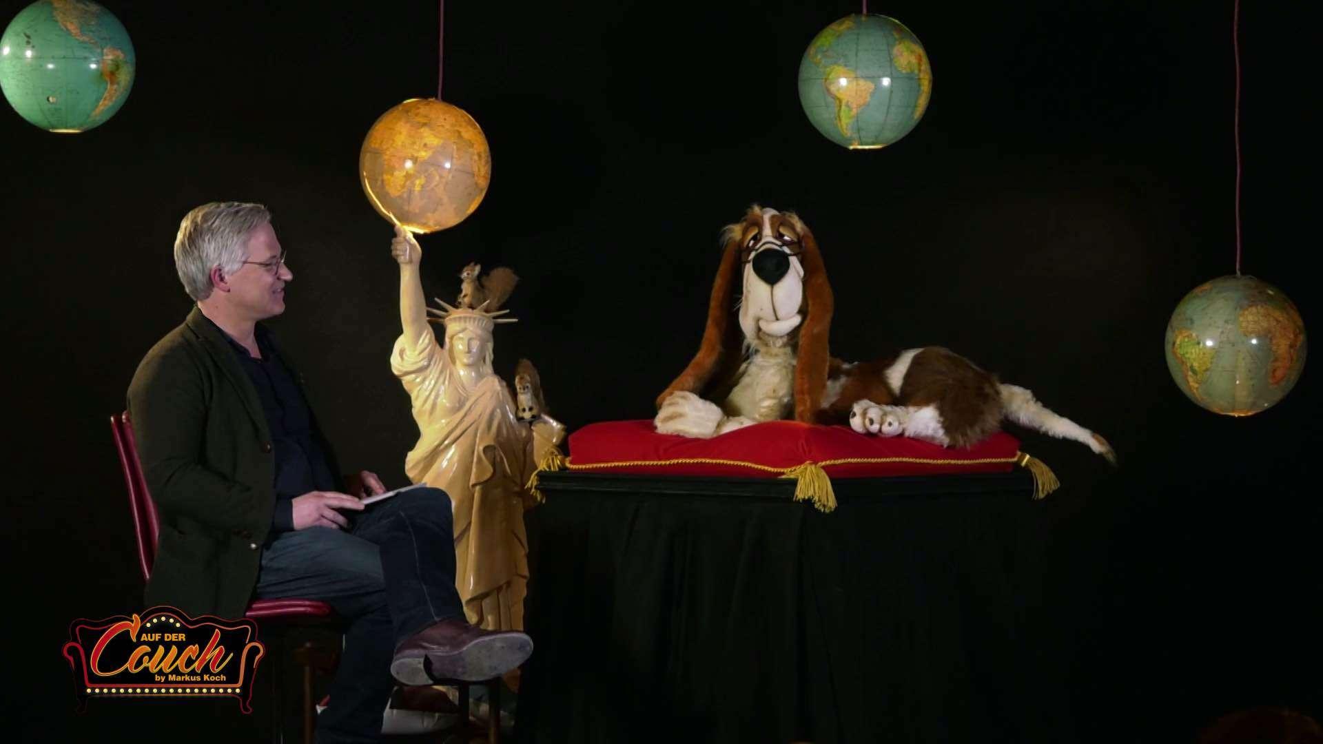 Markus Koch unterhält sich mit einem Kuscheltier Hund in seinem Studio von