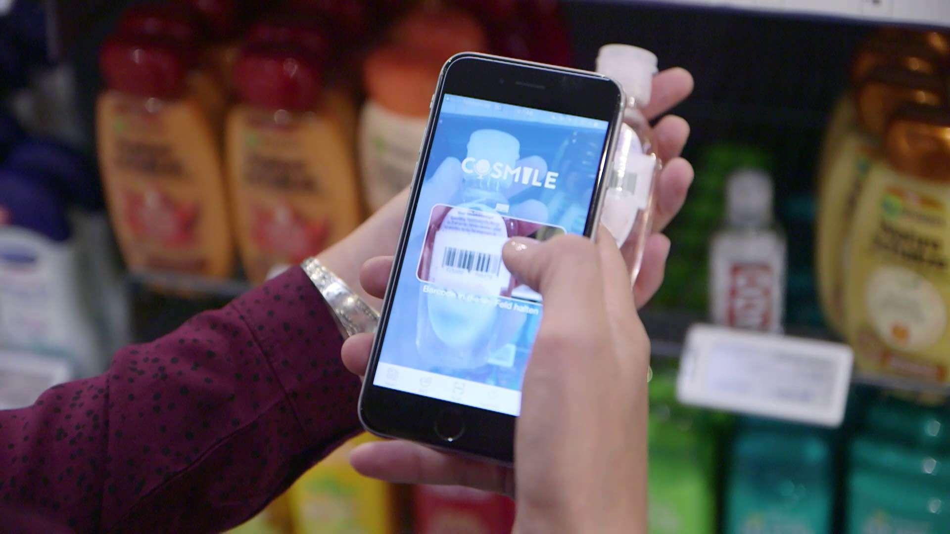 Eine Person fotografiert den Strichcode von einem Produkt in einem Geschäft