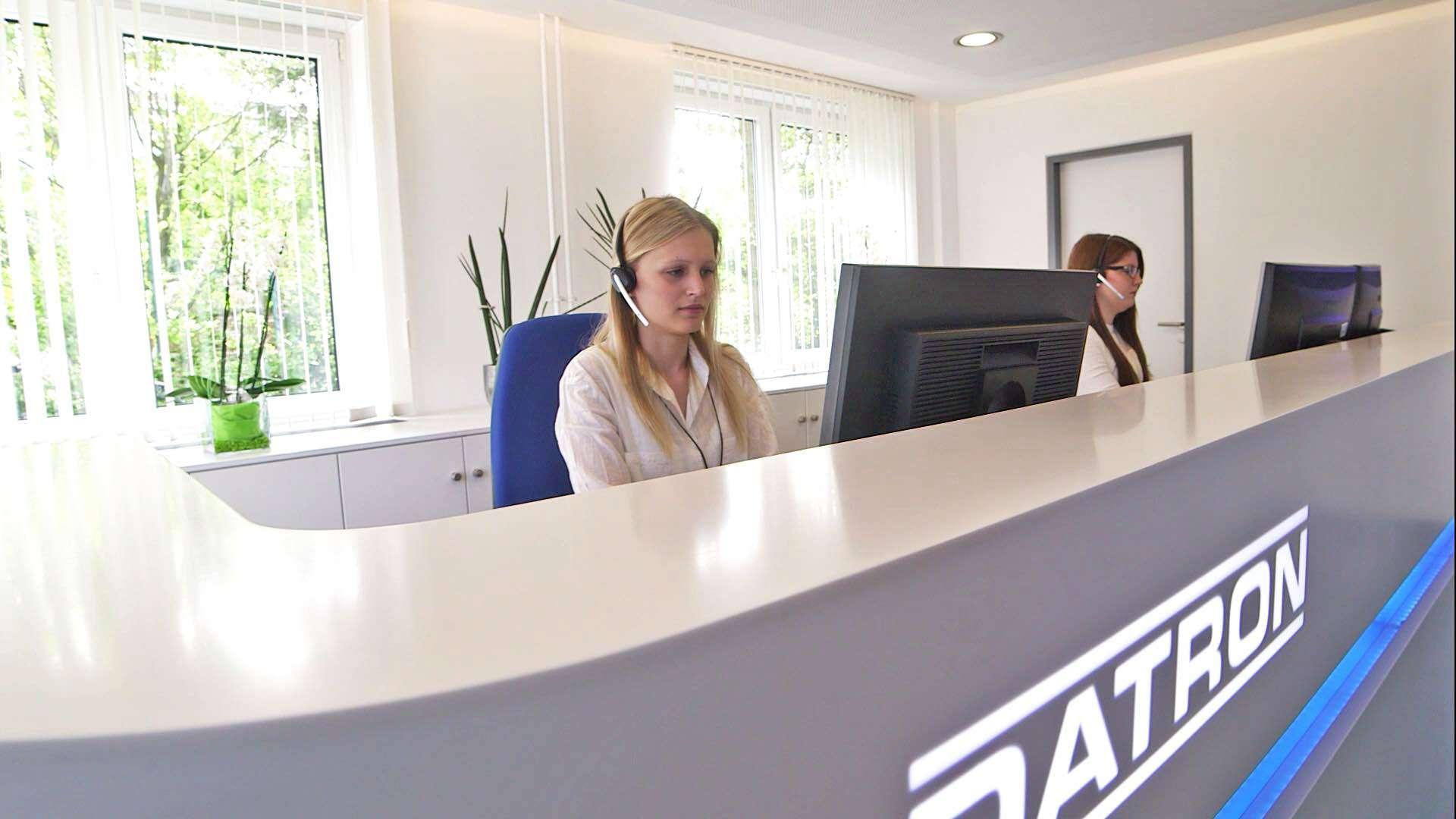 Zwei Mitarbeiterinnen des Unternehmens DATRON sitzen im Eingangsbereich der Firma und arbeiten an den Computern