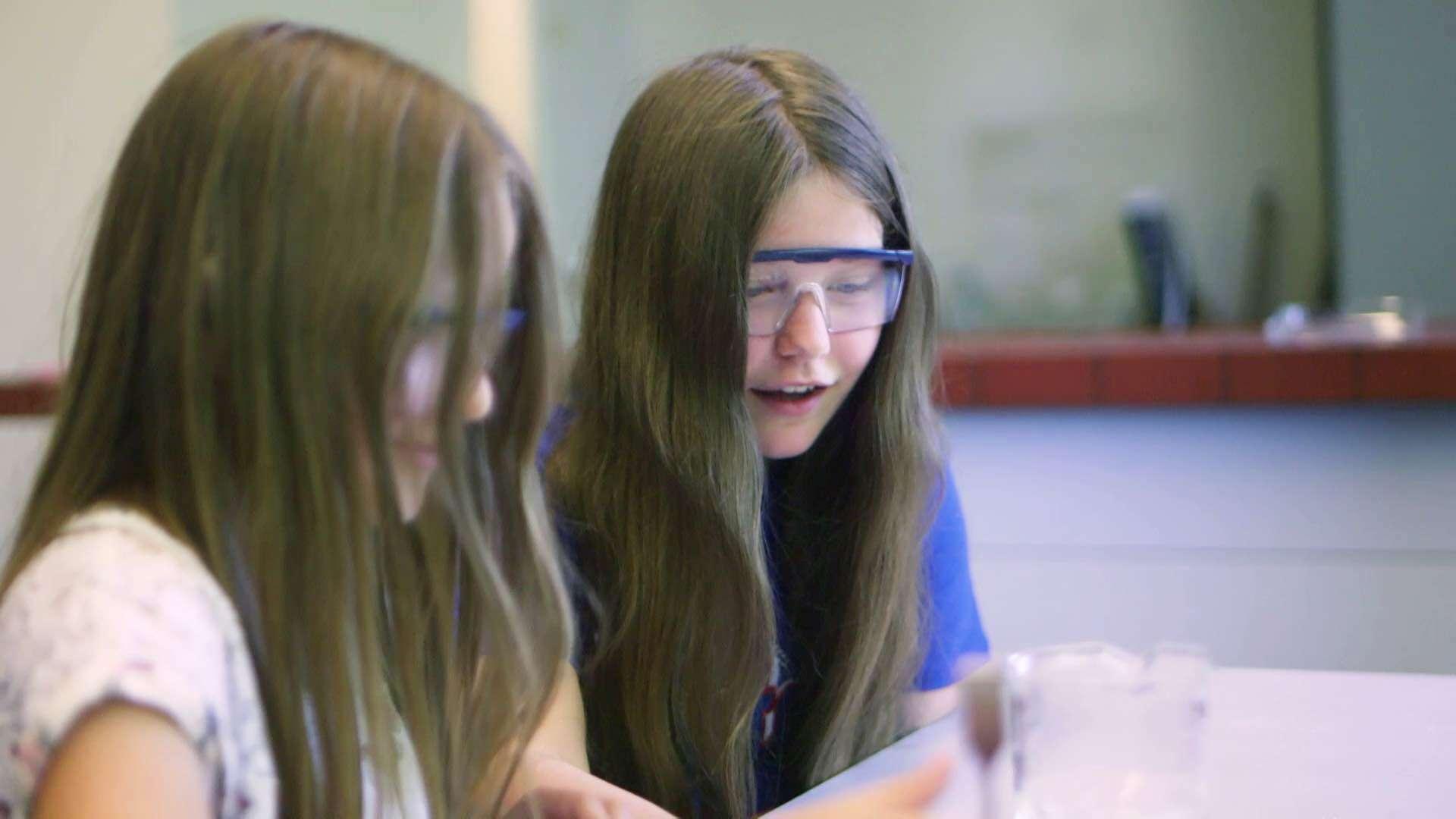 Zwei braunhaarige Mädchen sitzen mit Schutzbrillen in der Schule und machen ein Experiment
