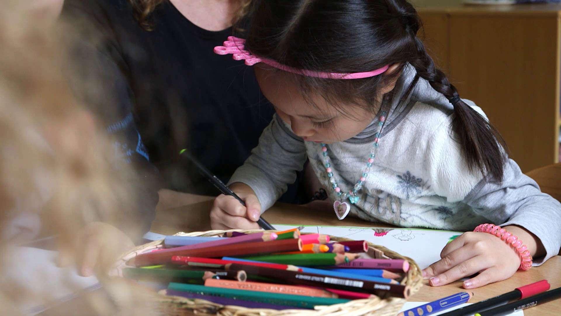 Ein kleines Mädchen hat viele Buntstifte vor sich liegen und malt ein Bild aus