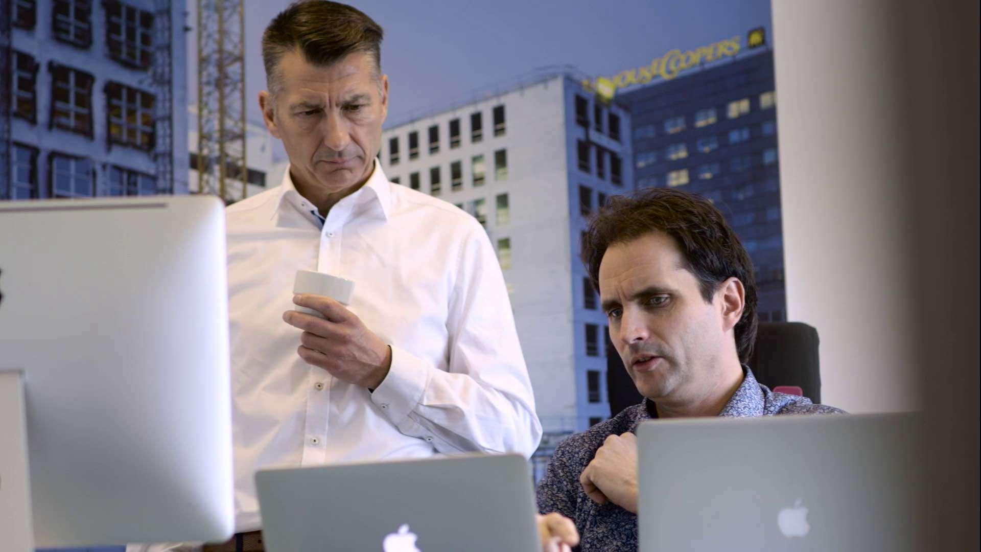 Zwei Männer schauen sich etwas auf Apple Computern an