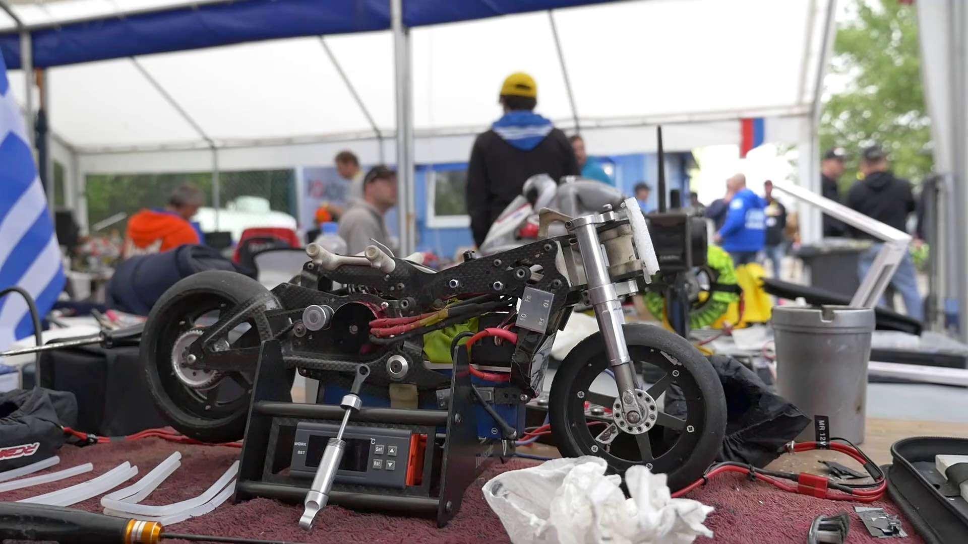 Ein Mini-Motorrad ist auf einem Tisch mit verschiedenem Werkzeug aufgebaut und im Hintergrund erkennt man viele Menschen