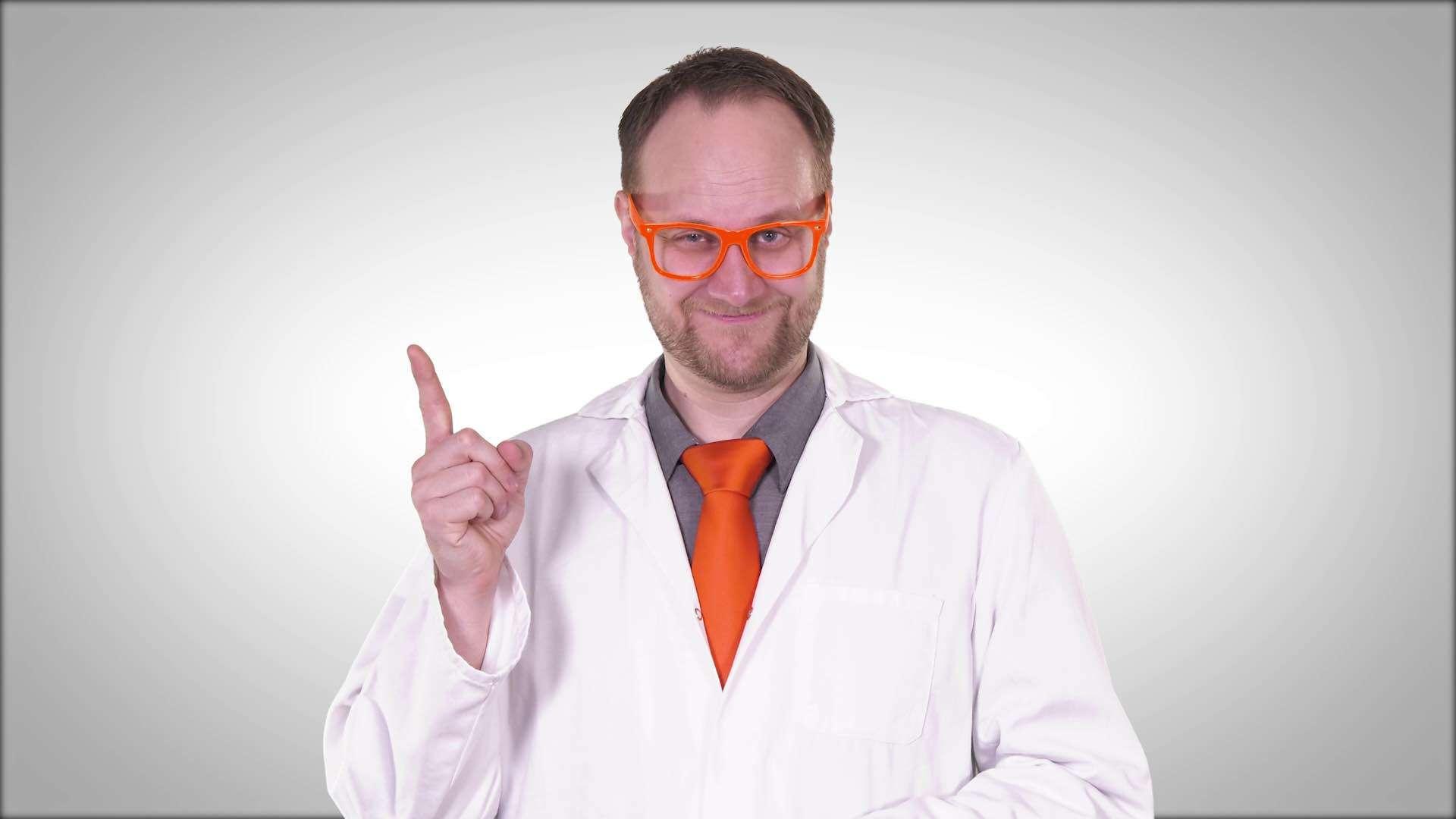Eine Mann mit orangefarbener Brille und Krawatte in einem Labor-Mantel hebt den rechten Zeigefinger