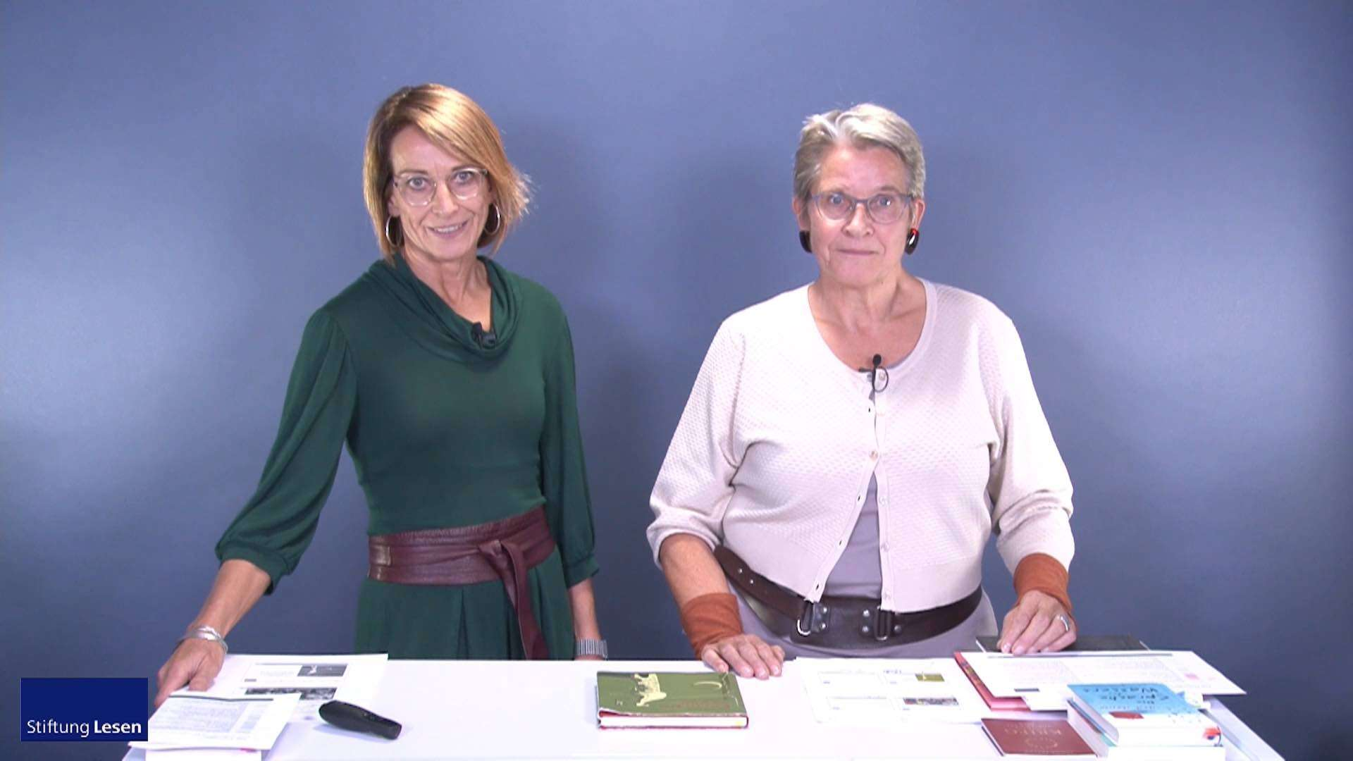 Zwei Frauen stehen hinter einem Tisch auf dem verschiedene Bücher und Prospekte liegen